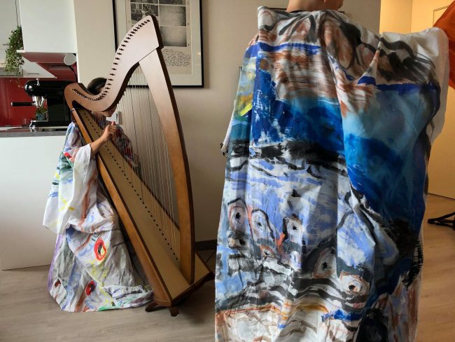 Two people in artistic clothing, one playing the harp. Photo.