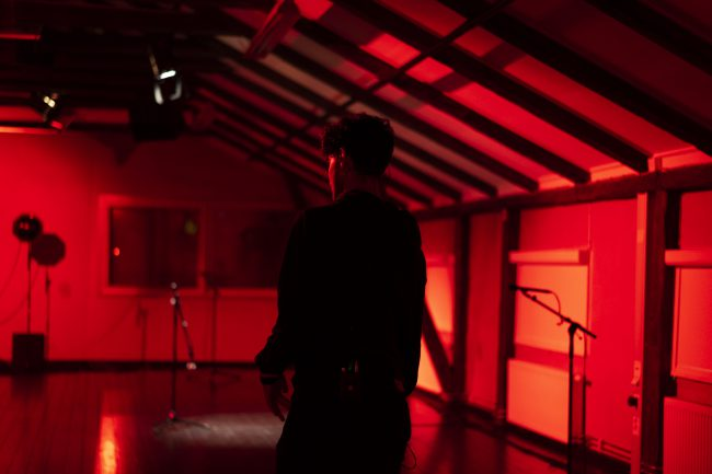 Man from behind in a red room. Photo.