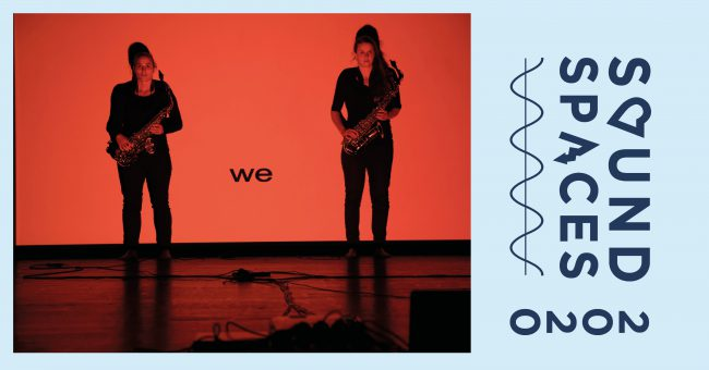 Two female artists with saxophones standing against a red background. Foto.