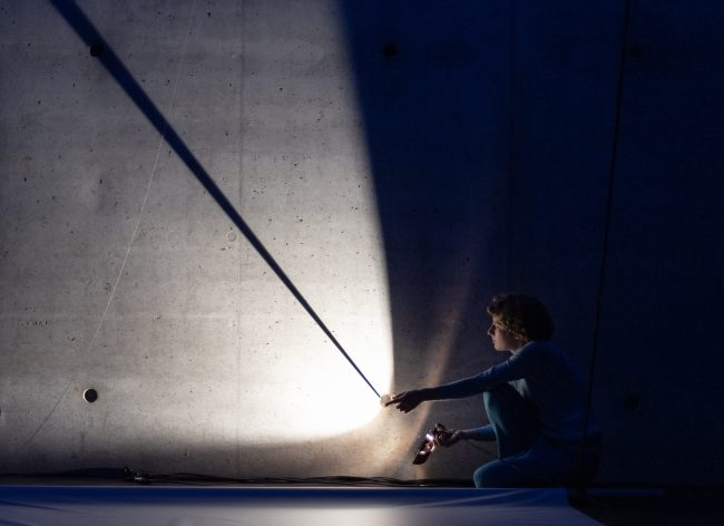The artist sits in a crouch and illuminates a gray concrete wall with a flashlight. Photo.
