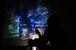 The artist makes a projection with light and various objects on the wall. Photo.