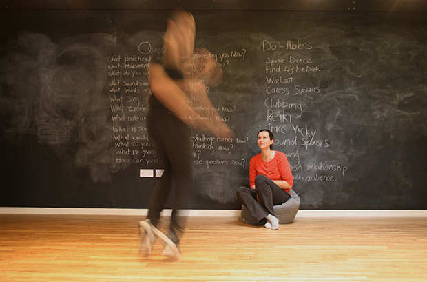Performing situation with one person jumping, the other sitting in front of a blackboard. Photo.