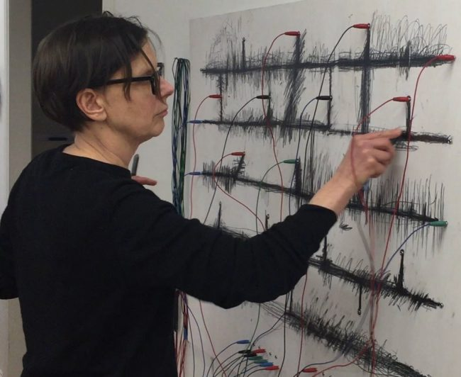 Ann Rosén draws on the wall with black chalk. Photo.
