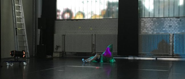 View into a room with person doing a performance. Foto.