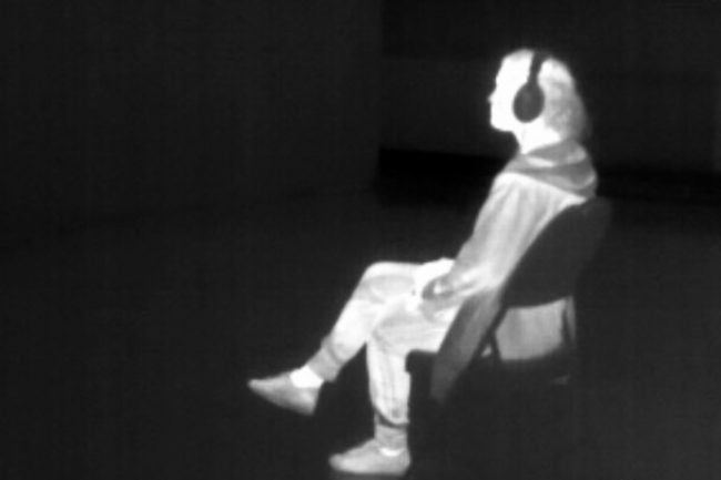 Negative photo of a seated man with headset. Photo.