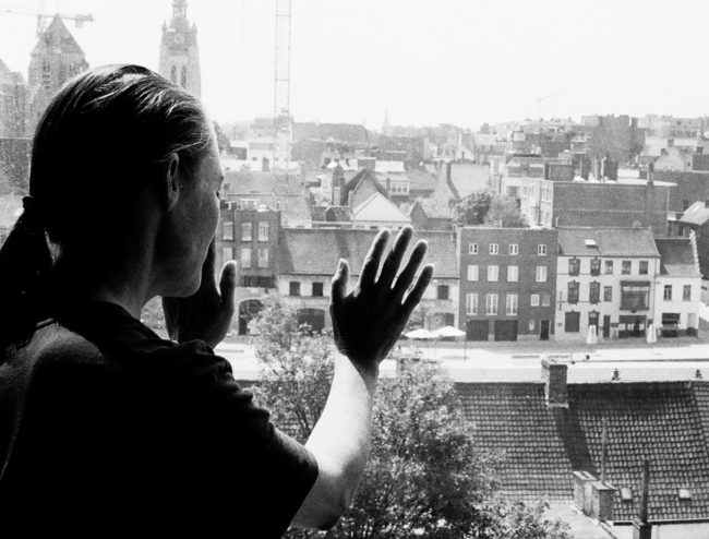 A woman who touches the window and looks at a city. Photo.