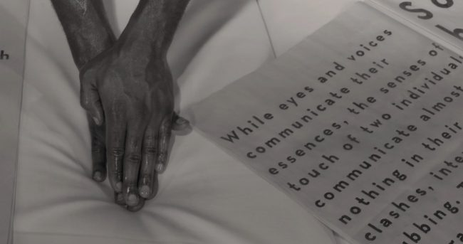 Hands lying on a white mattress next to a sheet of paper in black-and-white. Photo.