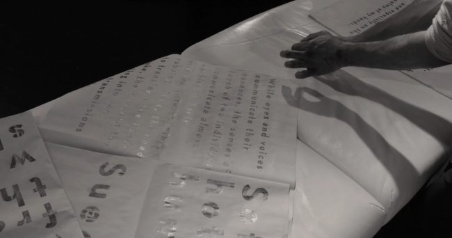 Hands on a white mattress flipping through a written piece of paper in black-and-white. Photo.