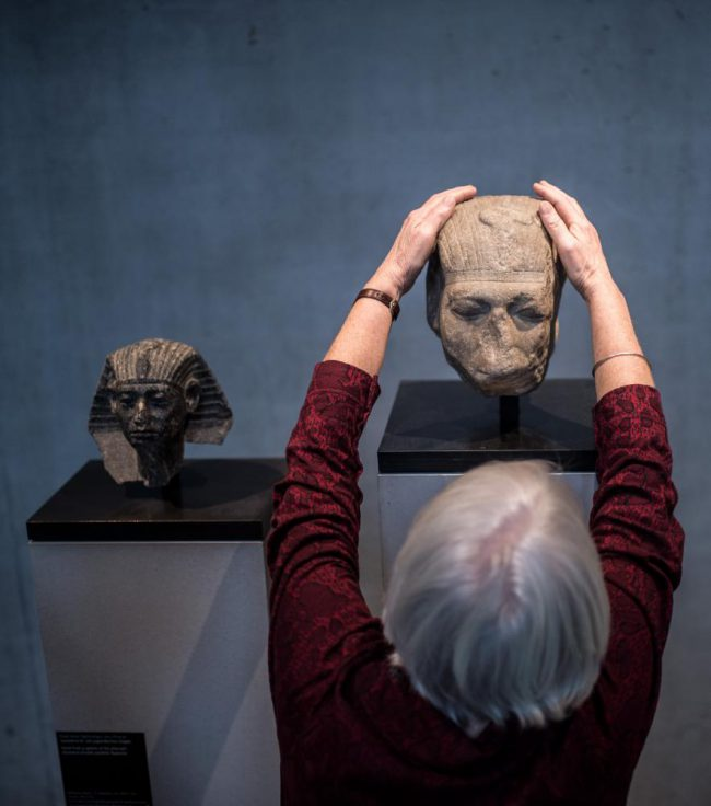 An elderly lady from behind touching an Egyptian head bust. Photo.