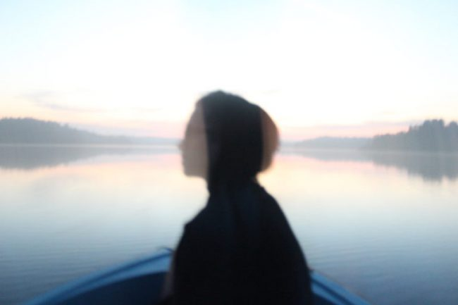 A blurred shot of a person in profile sitting in a boat on a lake. Photo.