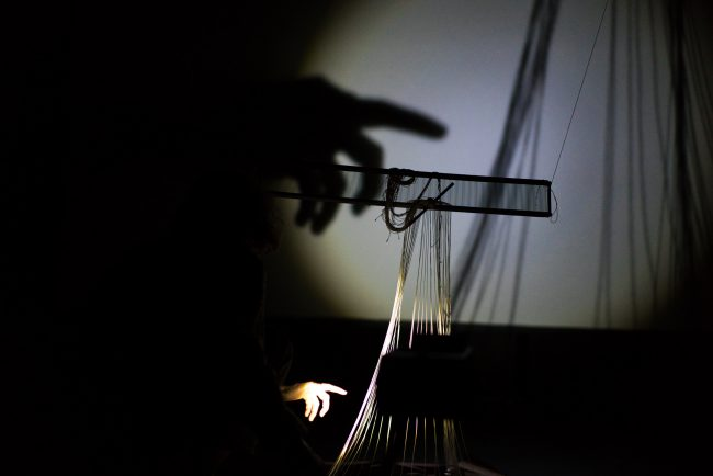 The artist's hand and objects are illuminated differently. Photo.