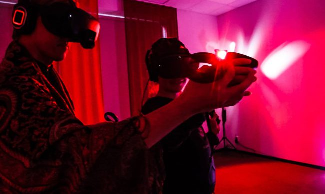 Two people wearing a VR headset and playing VR. Photo.