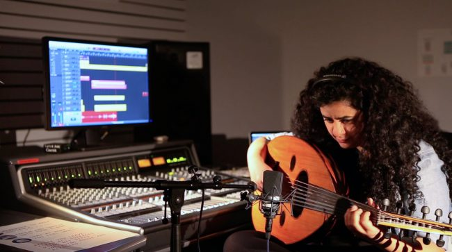 The artist sitting in the sound studio and playing the Oud instrument. Photo.