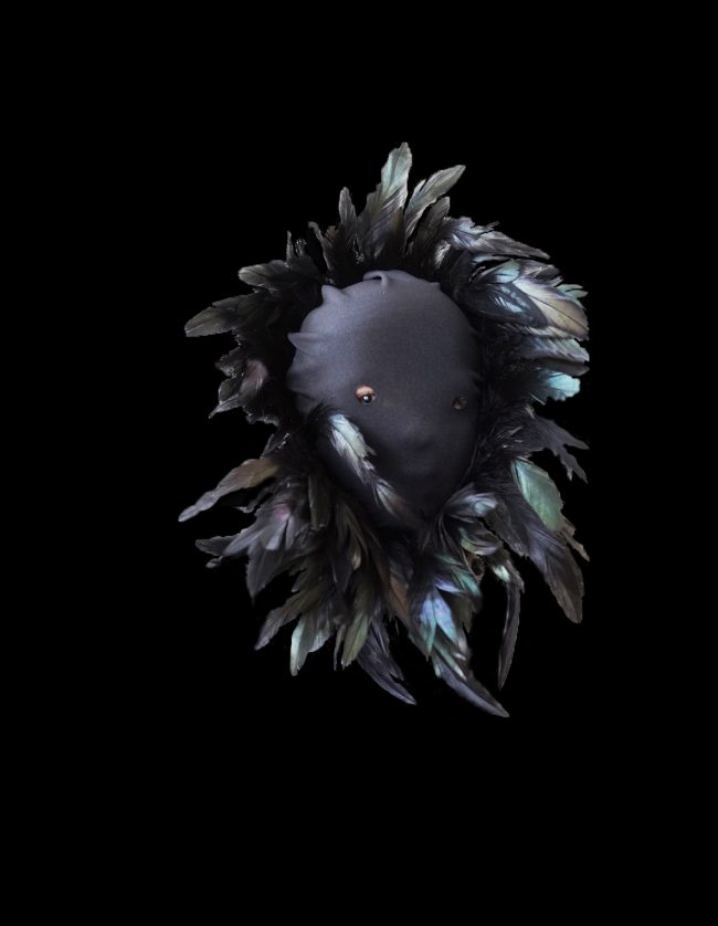 A masked head with feathers in front of a black background. Photo
