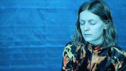 Emilia Gasiorek in front of a blue curtain, sitting. Photo.