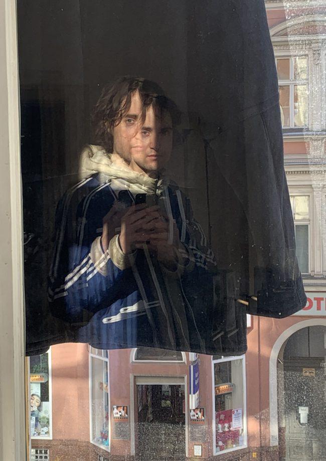 Selfie of Paolo Thorsen-Nagel taken in a window. Photo.