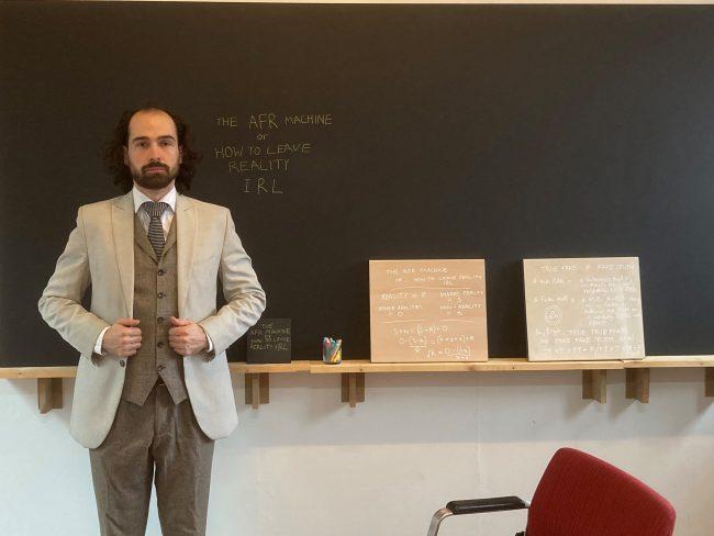 The artist next to a blackboard. Photo.
