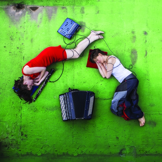 The artists lie on a green floor with headphones. Photo.