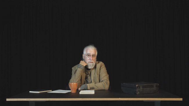 Man sitting at a desk. Photo.