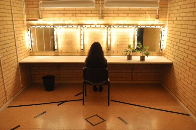 Woman sitting in front of mirrors. Photo.