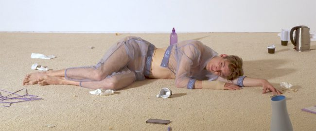 A man in transparent clothes lies on a moddy floor. Photo.